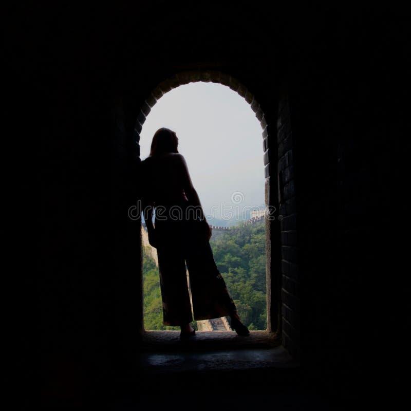 Silueta de la se?ora de pelo largo en llamaradas contra la Gran Muralla de China imagen de archivo