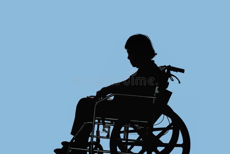 Silueta de la sentada mayor discapacitada y dejected de la mujer fotos de archivo