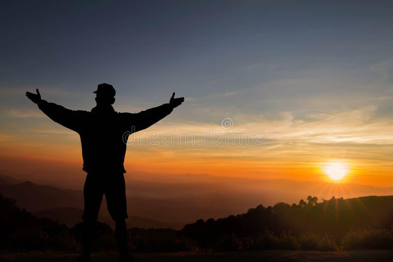 Silueta de la situación del hombre encima de la montaña con las manos aumentadas para arriba en fondo de la salida del sol, acert imagen de archivo