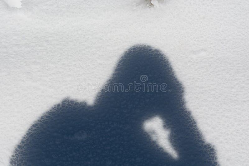 Silueta de la sombra en nieve congelada imagenes de archivo