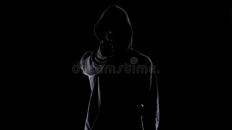 Silueta de la v?ctima masculina del tiroteo del asesino del contrato con el arma, crimen que conf?a foto de archivo