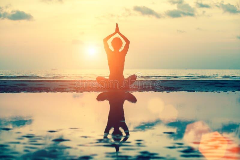 Silueta de la yoga Muchacha de la meditación en el fondo del mar durante puesta del sol foto de archivo