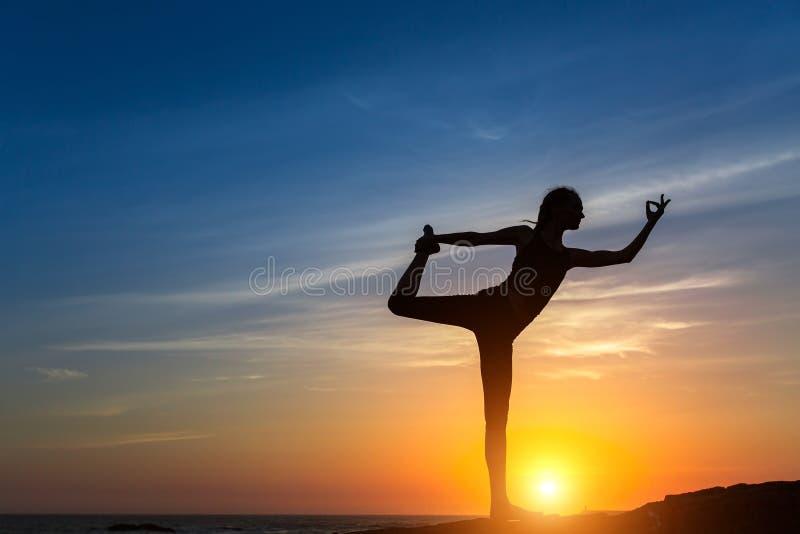 Silueta de la yoga Muchacha de la meditación en el mar durante puesta del sol foto de archivo libre de regalías