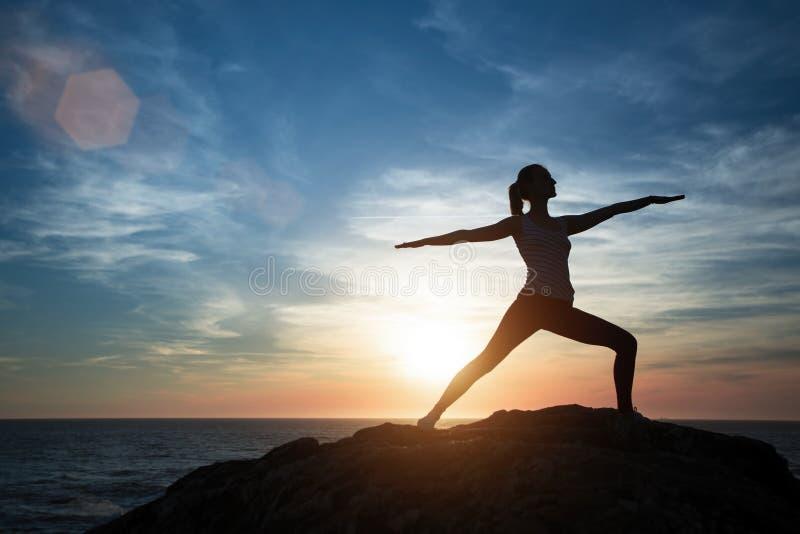 Silueta de la yoga Muchacha de la meditaci?n en el mar durante puesta del sol fotografía de archivo