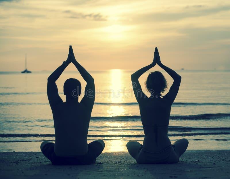 Silueta de la yoga practicante de los pares jovenes en la playa del mar durante puesta del sol fotografía de archivo