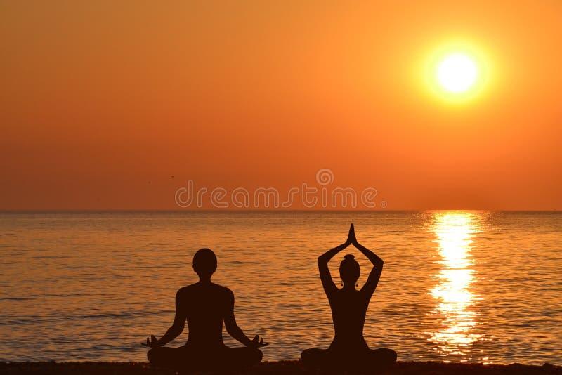 Silueta de la yoga practicante de la mujer y del hombre en la playa foto de archivo libre de regalías