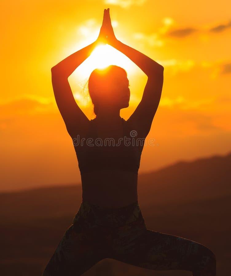 Silueta de la yoga practicante o de los pilates de la mujer joven en la puesta del sol o la salida del sol en la ubicación hermos fotos de archivo
