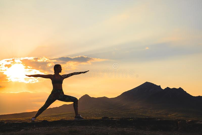 Silueta de la yoga practicante o de los pilates de la mujer joven en la puesta del sol o la salida del sol en la ubicación hermos fotos de archivo libres de regalías