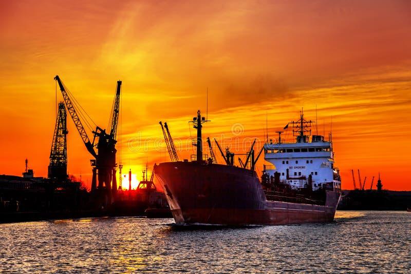 Silueta de las grúas del puerto marítimo sobre puesta del sol foto de archivo libre de regalías