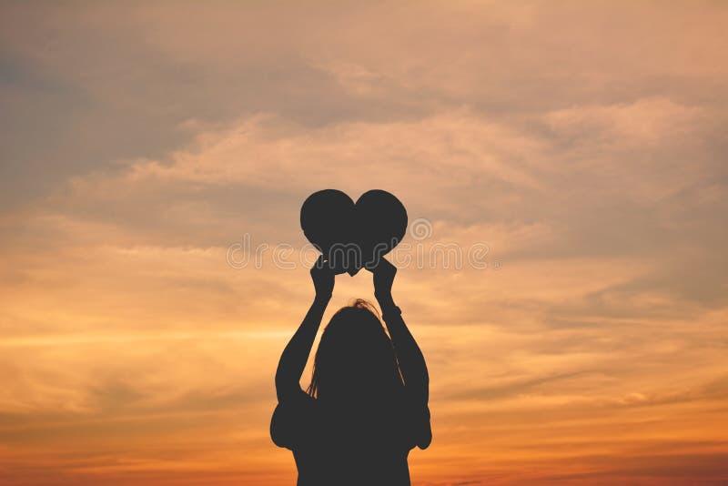 Silueta de las manos de las mujeres que llevan a cabo forma del corazón imágenes de archivo libres de regalías