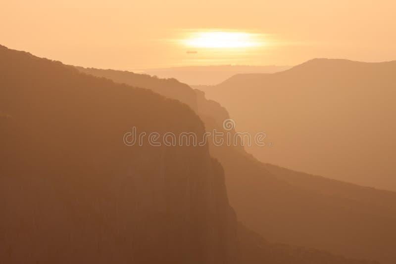 Silueta de las montañas crimeas durante una puesta del sol colorida y el Mar Negro en el fondo imagen de archivo