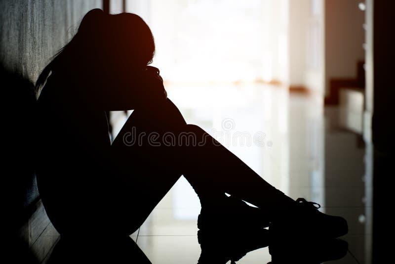 Silueta de las mujeres tristes y deprimidas que se sientan en la calzada del condominio o de la oficina foto de archivo