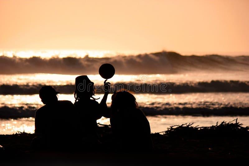 Silueta de los amigos jovenes que juegan con una bola en la playa en puesta del sol imagen de archivo libre de regalías