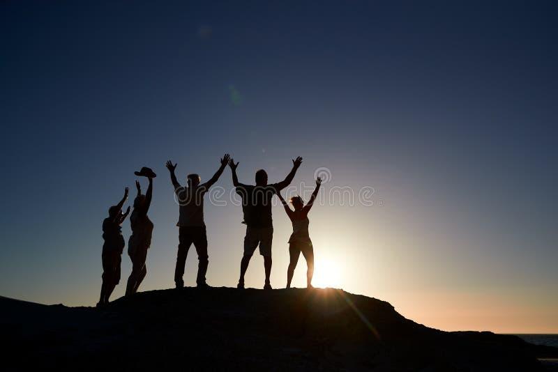 Silueta de los amigos mayores que se colocan en rocas por el mar de vacaciones en la puesta del sol con los brazos extendidos imagen de archivo libre de regalías