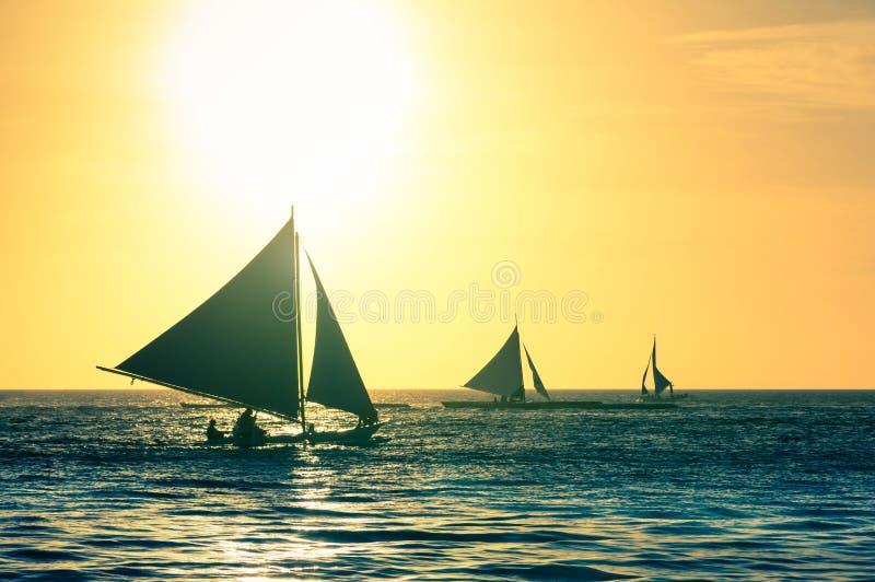Silueta de los barcos de navegación típicos en la puesta del sol en la isla de Boracay foto de archivo