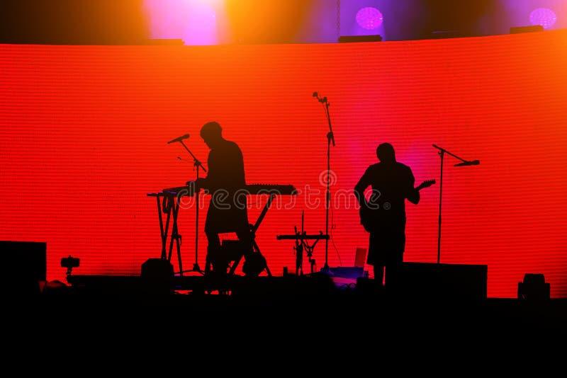 Silueta de los músicos de banda de rock en etapa, del guitarrista y del teclista en fondo rojo imagen de archivo