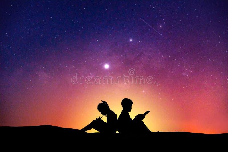 Silueta de los niños que leen un libro en la vía láctea del cielo foto de archivo libre de regalías