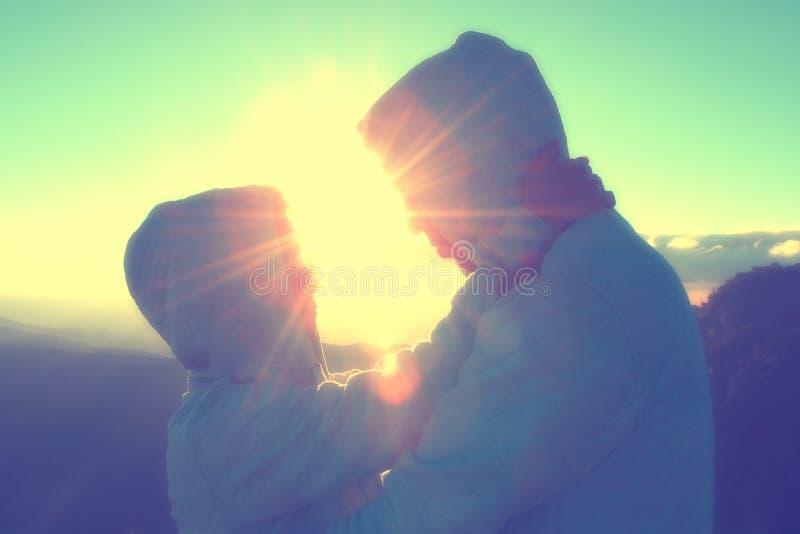 Silueta de los pares felices en la niebla y el sol escénicos de la montaña imagen de archivo