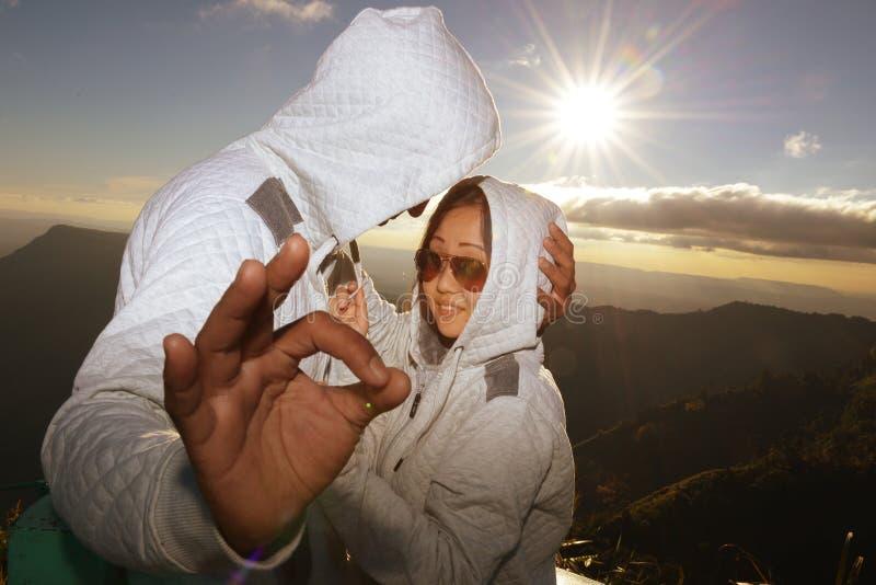 Silueta de los pares felices en la niebla y el sol escénicos de la montaña imagenes de archivo