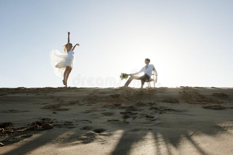 Silueta de los pares hermosos jovenes que cuelgan hacia fuera junto en la playa imagen de archivo