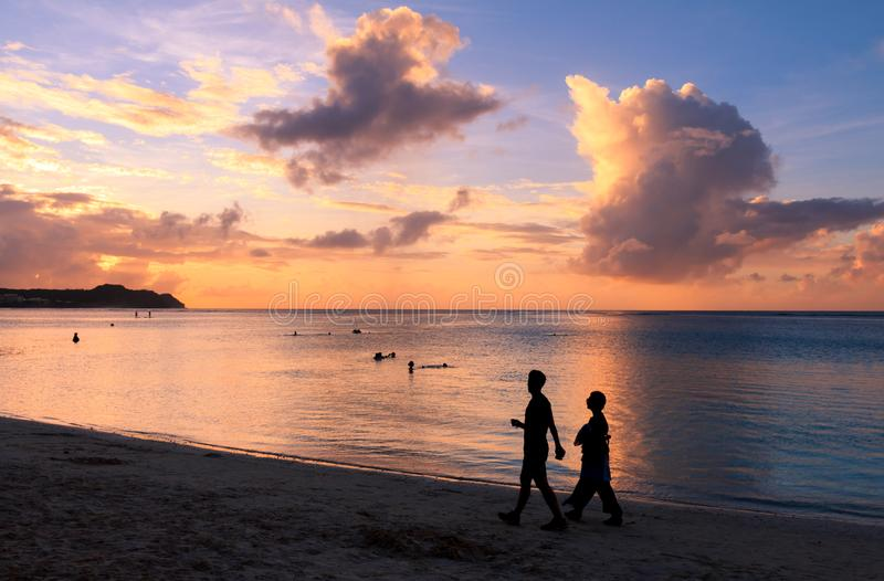 Silueta de los pares que caminan en la playa en la puesta del sol fotos de archivo