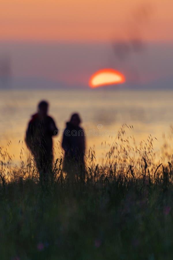 Silueta de los pares que caminan por la costa y que miran el sol poniente fotos de archivo