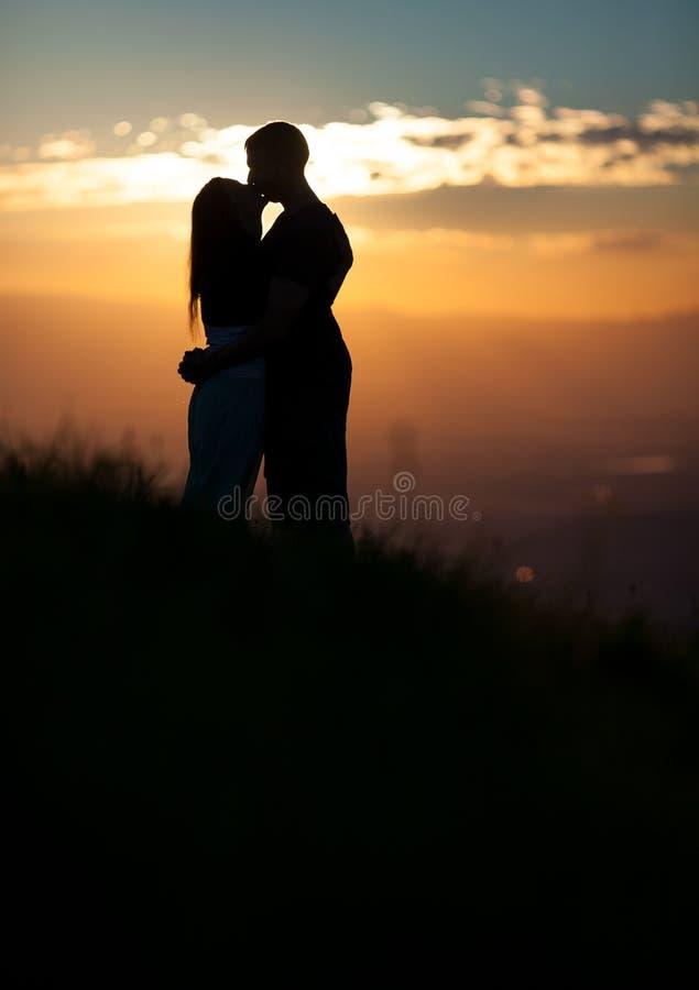 Silueta de los pares que se besan en puesta del sol fotografía de archivo