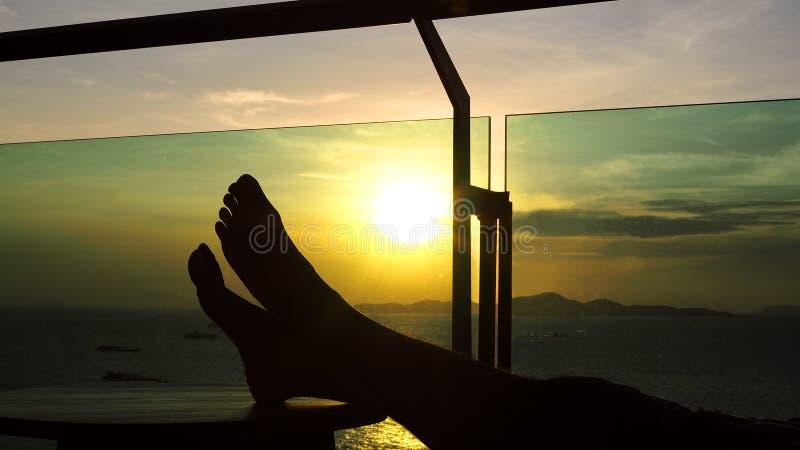 Silueta de los pies de un hombre que descansan sobre una tabla de madera con una puesta del sol hermosa de la tarde por el océano fotografía de archivo libre de regalías