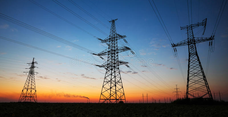 Silueta de los pilones de la electricidad y de las líneas eléctricas de alto voltaje fotografía de archivo libre de regalías