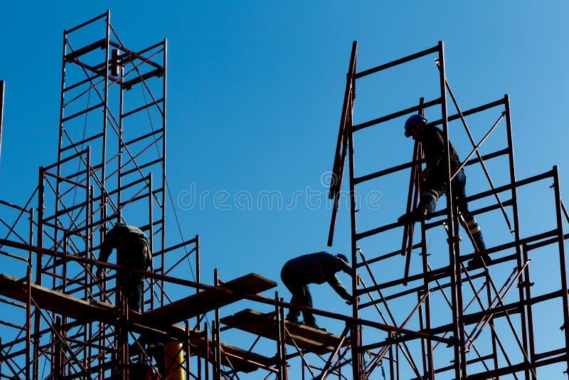 Silueta de los trabajadores de construcción contra el cielo en los wi del andamio imágenes de archivo libres de regalías