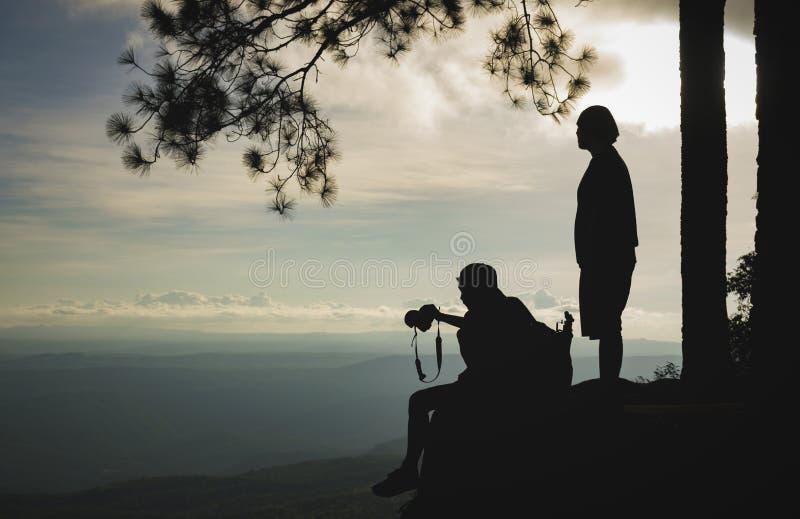 Silueta de los viajeros que disfrutan de un Mountain View hermoso imagen de archivo