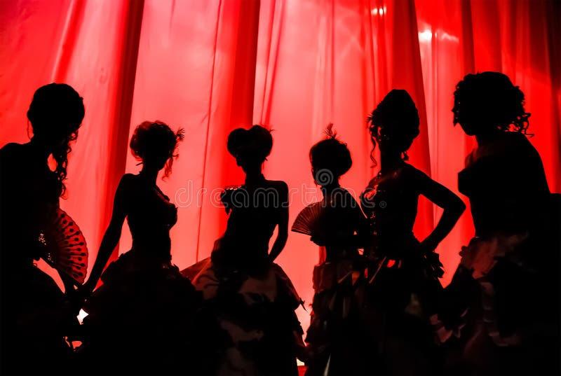 Silueta de muchachas y de mujeres en trajes del carnaval y vestidos de bola en el teatro en la etapa detrás de la cortina roja foto de archivo libre de regalías