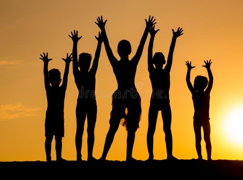 Silueta de niños contra puesta del sol imagenes de archivo