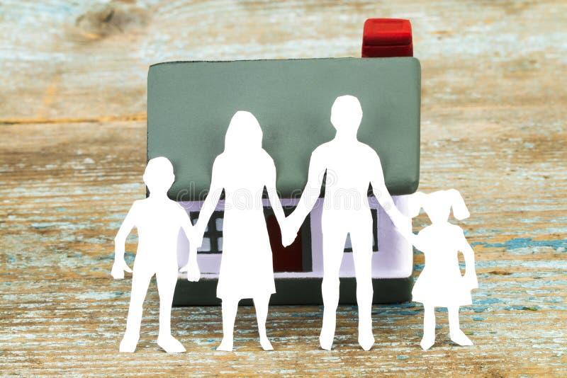 Silueta de papel de la familia y de la casa en el escritorio de madera seguro foto de archivo libre de regalías
