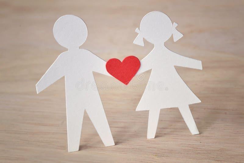 Silueta de papel de niños con un corazón - amor de la niñez concentrado foto de archivo libre de regalías