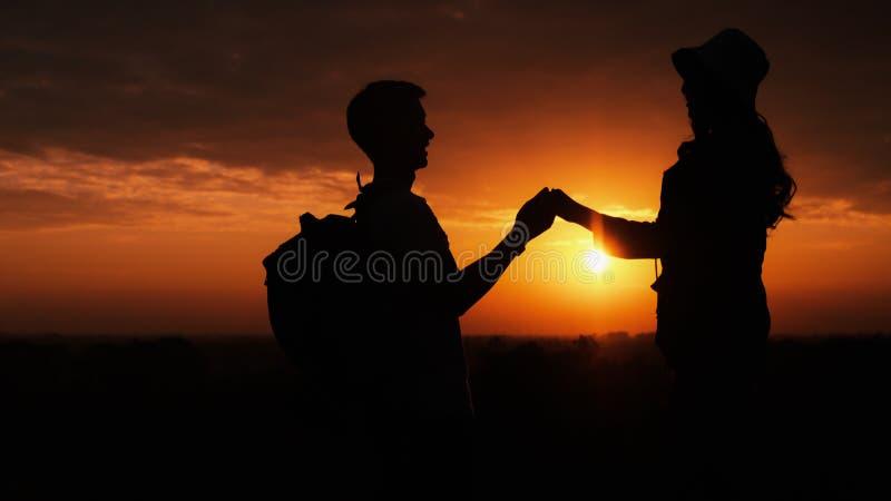 Silueta de pareja amante teniendo un momento romántico codo a codo con el sol de fondo og imagenes de archivo