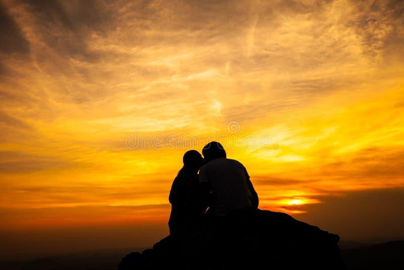 Silueta de pares cariñosos en puesta del sol foto de archivo libre de regalías