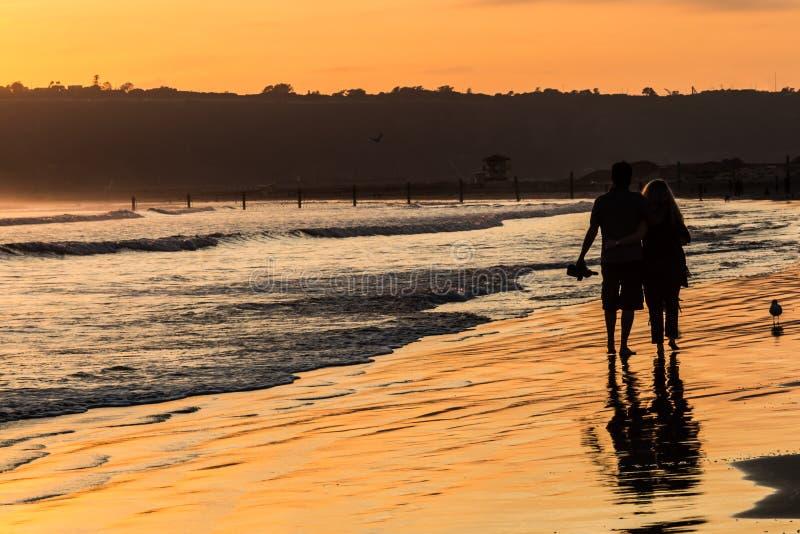 Silueta de pares en luz de oro en la playa fotos de archivo