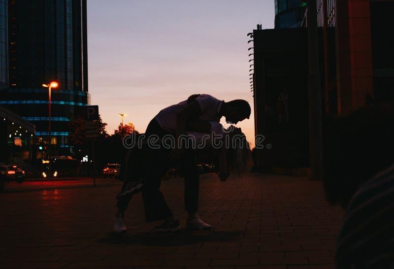 Silueta de pares felices jovenes en el amor que baila en la calle de la ciudad en la puesta del sol fotos de archivo