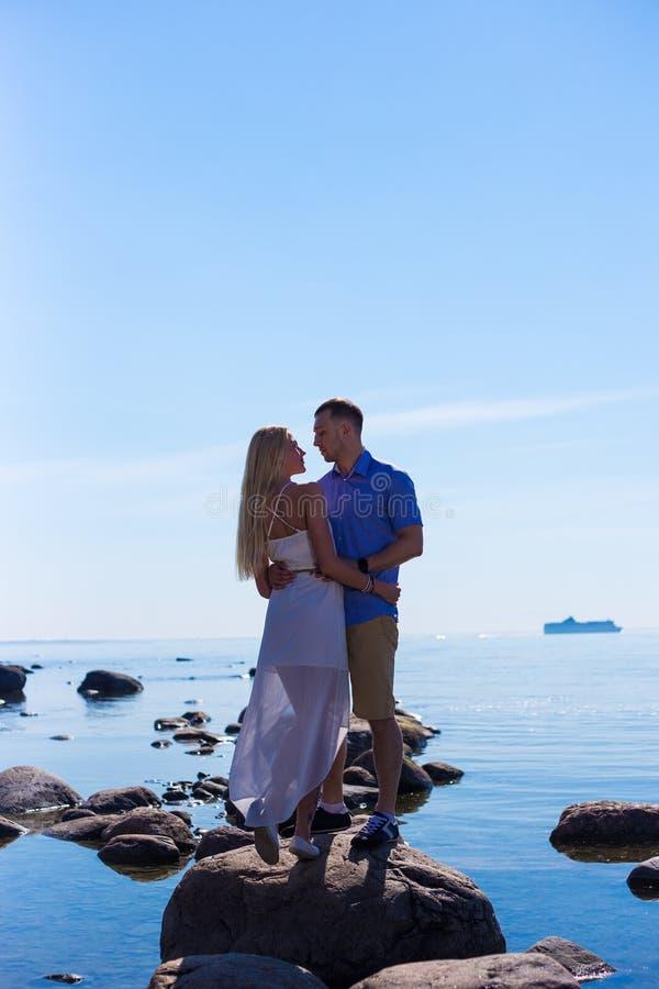 Silueta de pares jovenes en amor sobre fondo del mar fotografía de archivo libre de regalías