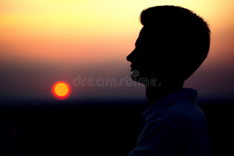 Silueta de rofile de una cara del ` s del hombre joven en la puesta del sol en un campo imagen de archivo