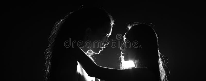 Silueta de sostenerse que se besa de la mujer atractiva dos en oscuridad a través fotos de archivo