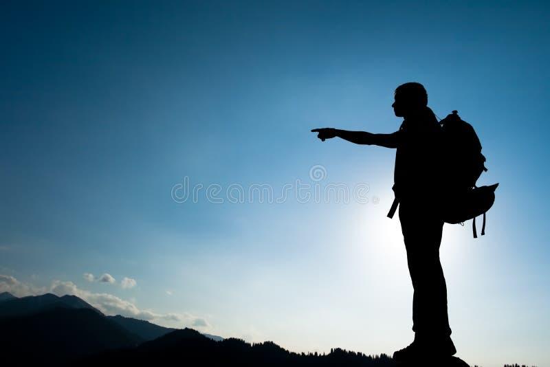 Silueta de subir a adulto joven en la cima de la cumbre imagen de archivo