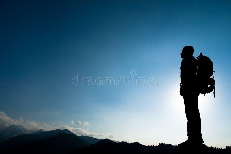 Silueta de subir a adulto joven en la cima de la cumbre fotografía de archivo