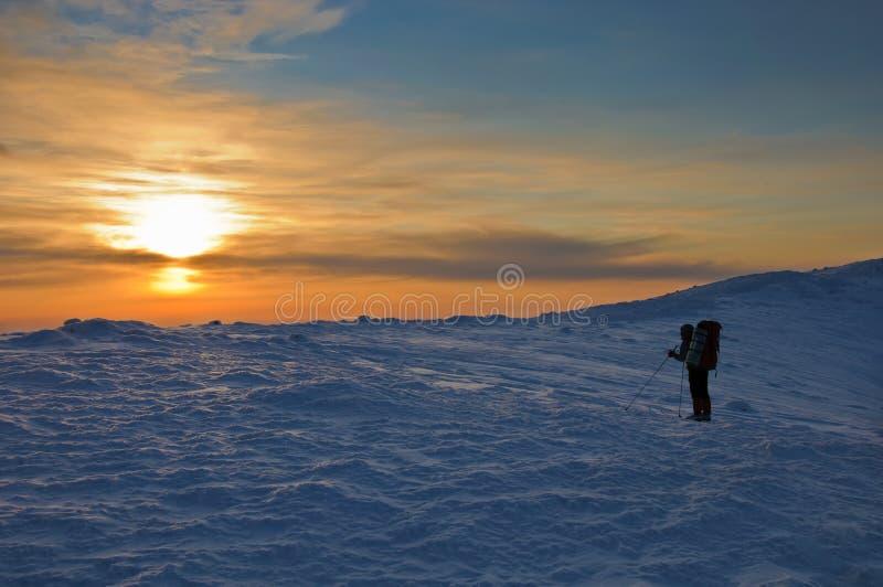 Silueta de Trekker en la puesta del sol en las montañas imagenes de archivo