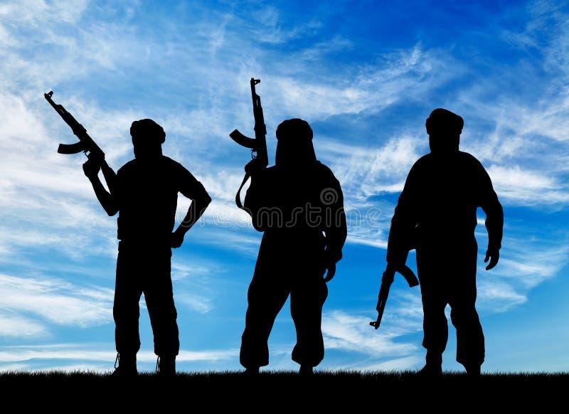 Silueta de tres terroristas foto de archivo libre de regalías