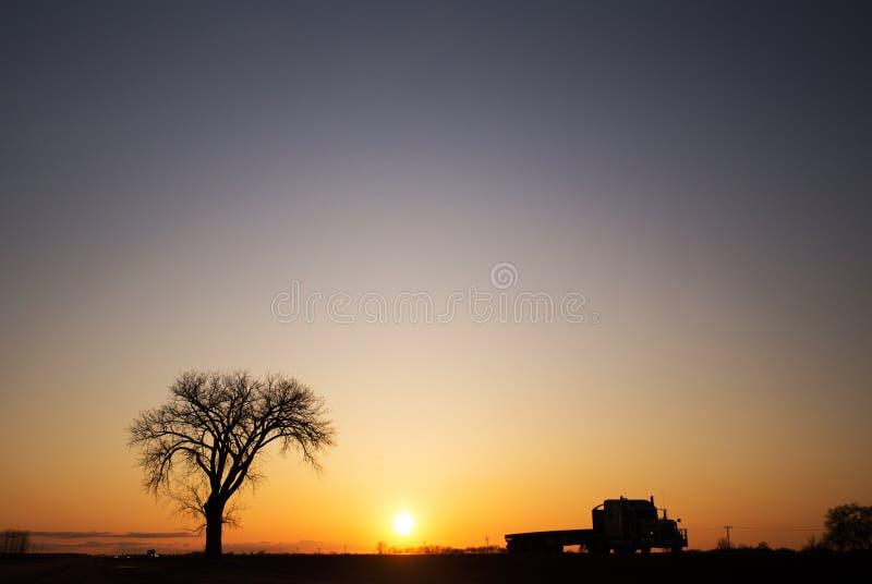Silueta de un árbol y semi camión en la puesta del sol fotos de archivo