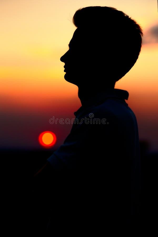 silueta de un adolescente de los deportes en la puesta del sol en un campo, perfil de una cara del hombre fotografía de archivo libre de regalías