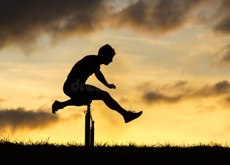 Silueta de un atleta en vallar fotografía de archivo libre de regalías