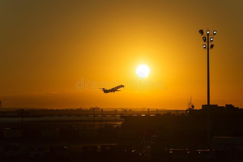 Silueta de un avión en la puesta del sol en aeropuerto fotografía de archivo libre de regalías